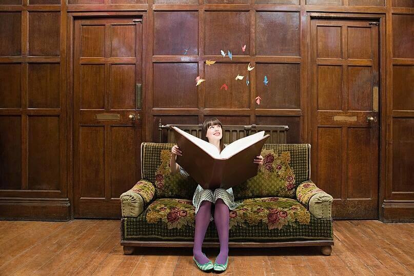 mulher com livro grande em um conto de fadas