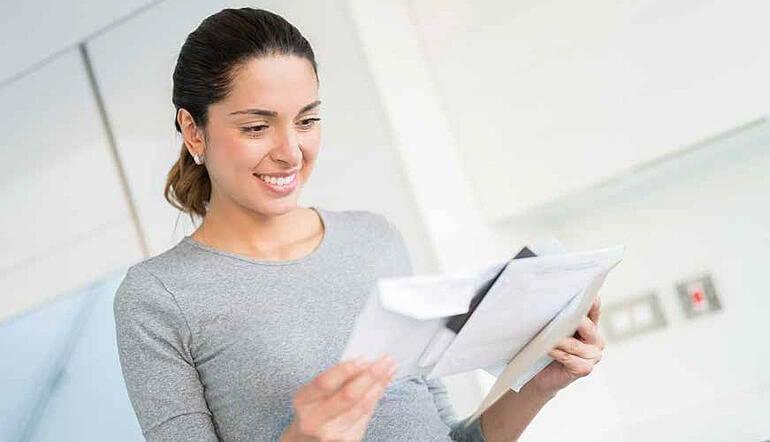 mulher abrindo uma carta sorrindo