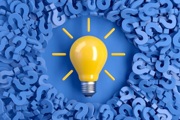 lâmpada no meio de várias interrogações
