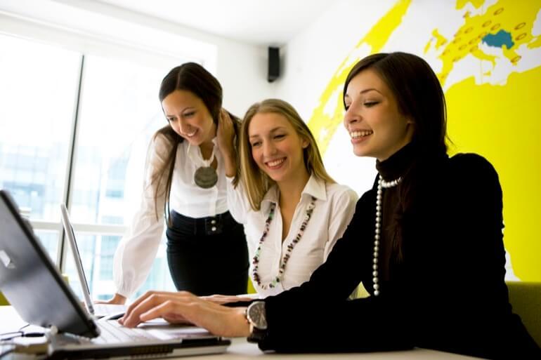 três mulheres sorrindo ao computador