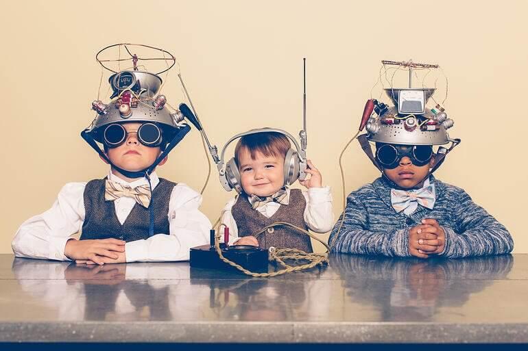 três crianças vestidas de cientistas em uma mesa