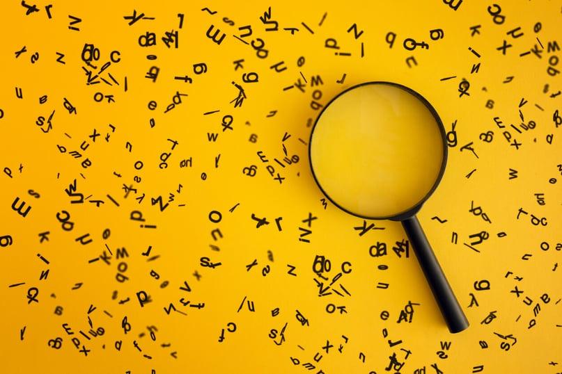 Lupa em fundo amarelo com letras espalhadas