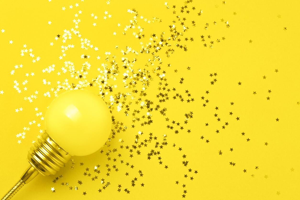 Lampada em fundo amarelo com pequenas estrelas