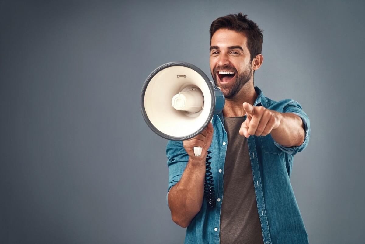 homem falando em um megafone e apontando para frente